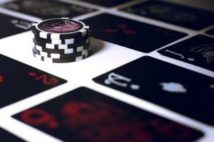 Image of poker chips on a table with cards